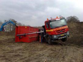 Vrachtwagen kantelt, lading in de sloot