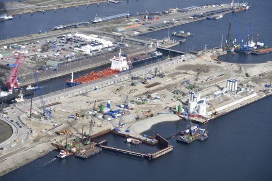290.000 m3 beton is er nodig om de nieuwe zeesluis te bouwen. OpenIJ koos voor betoncentrales op het sluiseiland (rechts op de foto). Vrachtwagens hoeven maar een korte afstand af te leggen van de centrales naar de bouwplaats. (Foto: Topview Fotografie)
