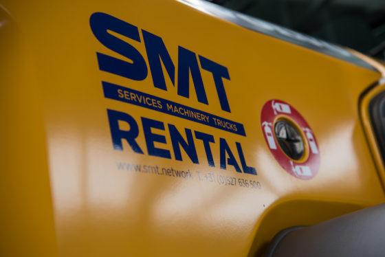 Het SMT-logo is al te zien op diverse machines voor de verhuur, en op onderhoudsbussen van monteurs.