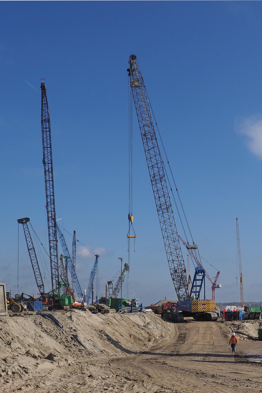 <p>Dat de werkruimte krap is illustreert deze foto. Talloze machines doen op een betrekkelijk klein oppervlak hun werk. Dagelijks werken 400 à 500 mensen aan de bouw van de zeesluis, 24 uur per dag en zeven dagen in de week. (Foto: Ko van Leeuwen)</p>