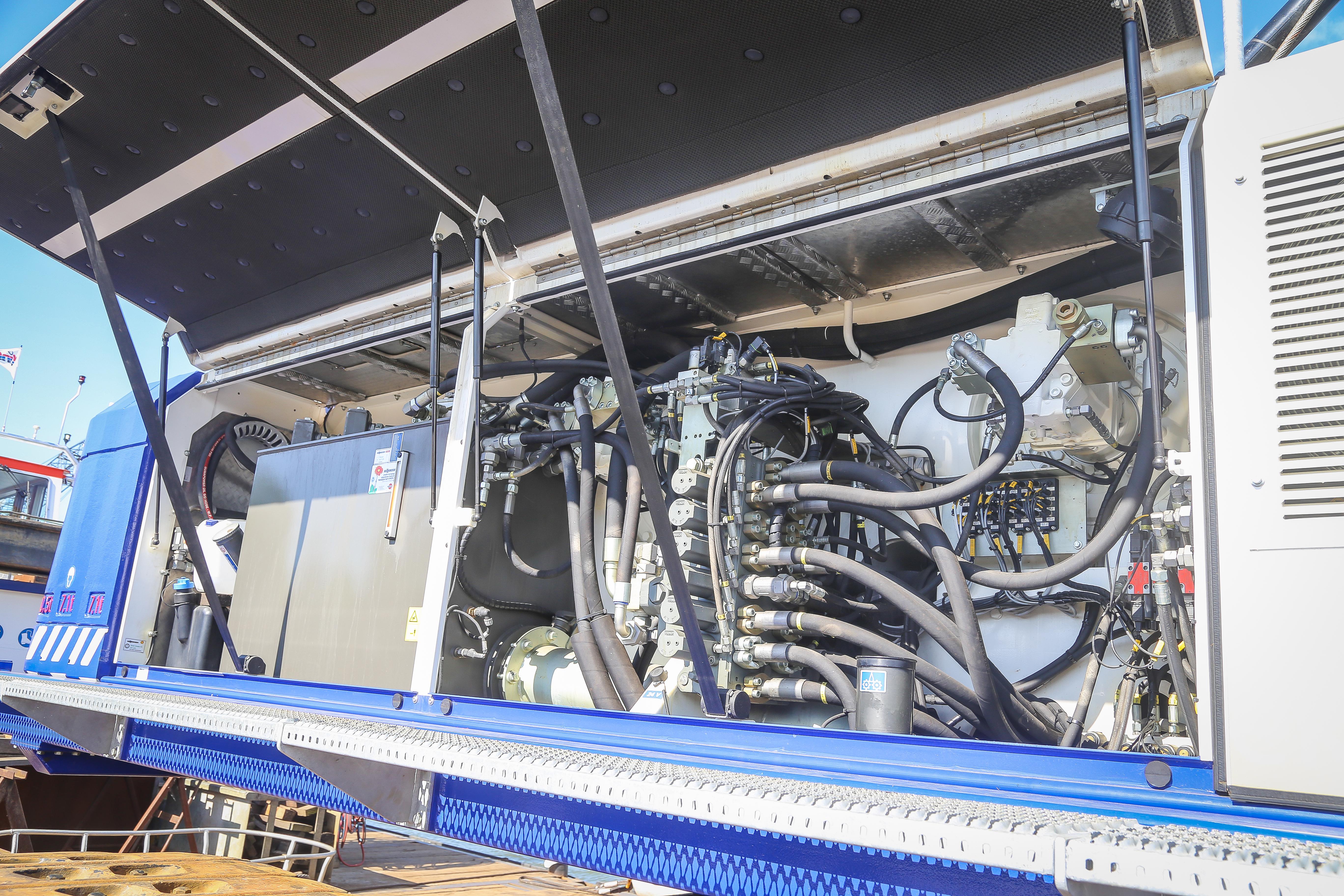 <p>Aan de rechterzijde is het ventielenblok te vinden. Alle slangen en kabels zijn gecodeerd, wat handig is voor de monteur. Tevens hier te vinden zijn de AdBluetank, brandstoftank met vulpomp en op de voorgrond de hydrauliektank afgevuld met bio-olie. </p>