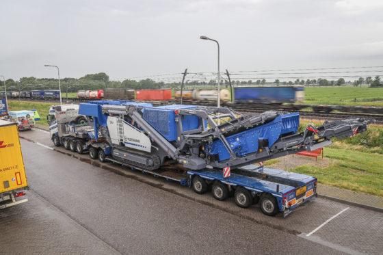 De lading bestaat vandaag uit een 56 tons Kleemann breker (MR110Z). Ondanks een combinatiegewicht van 100 ton slaat de I-shift-bak de kruipversnellingen op vlak terrein gewoon over.