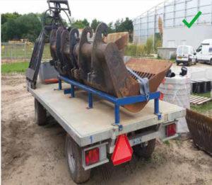 Ook toegestaan: een graafbak vastsjorren op een aanhangwagen voordat deze wordt verplaatst.