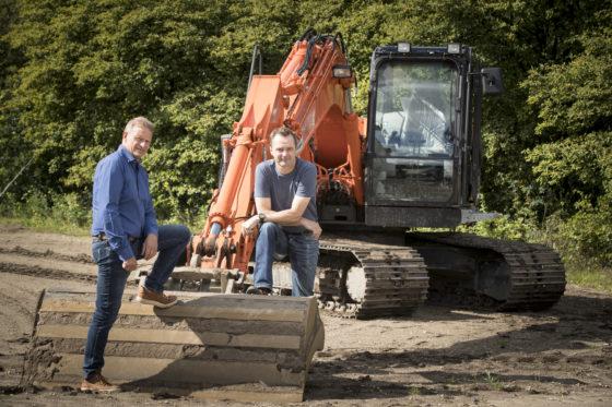 Johan van Apeldoorn(links)en Pim de Jonge bij een Hitachi ZX 135 US-5, die bij de opleiding tot machinistdoorIPCWerkt wordt ingezet. 'Wij leiden mensen praktisch op. Geen saaie theorielessen, maar zelf op de graafmachine of wiellader.'