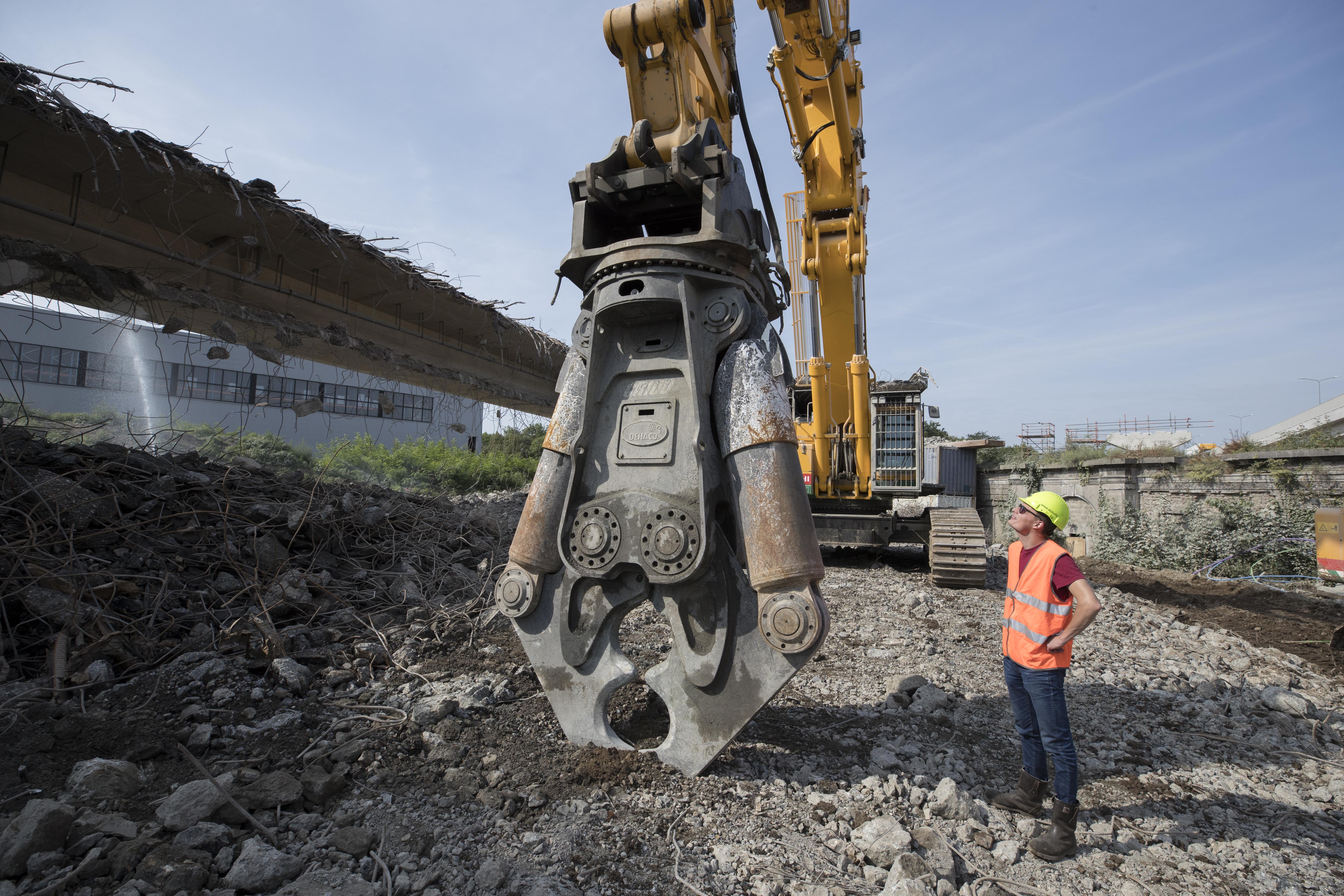 <p>TristanSwaninkvan STC Coevorden naast de doorDehacogeleverdeCR100R betonschaar. Dit uitrustingsstuk weegt bijna 12 ton, heeft een sluitkracht van 400 ton een bekopening van 2 meter.</p>