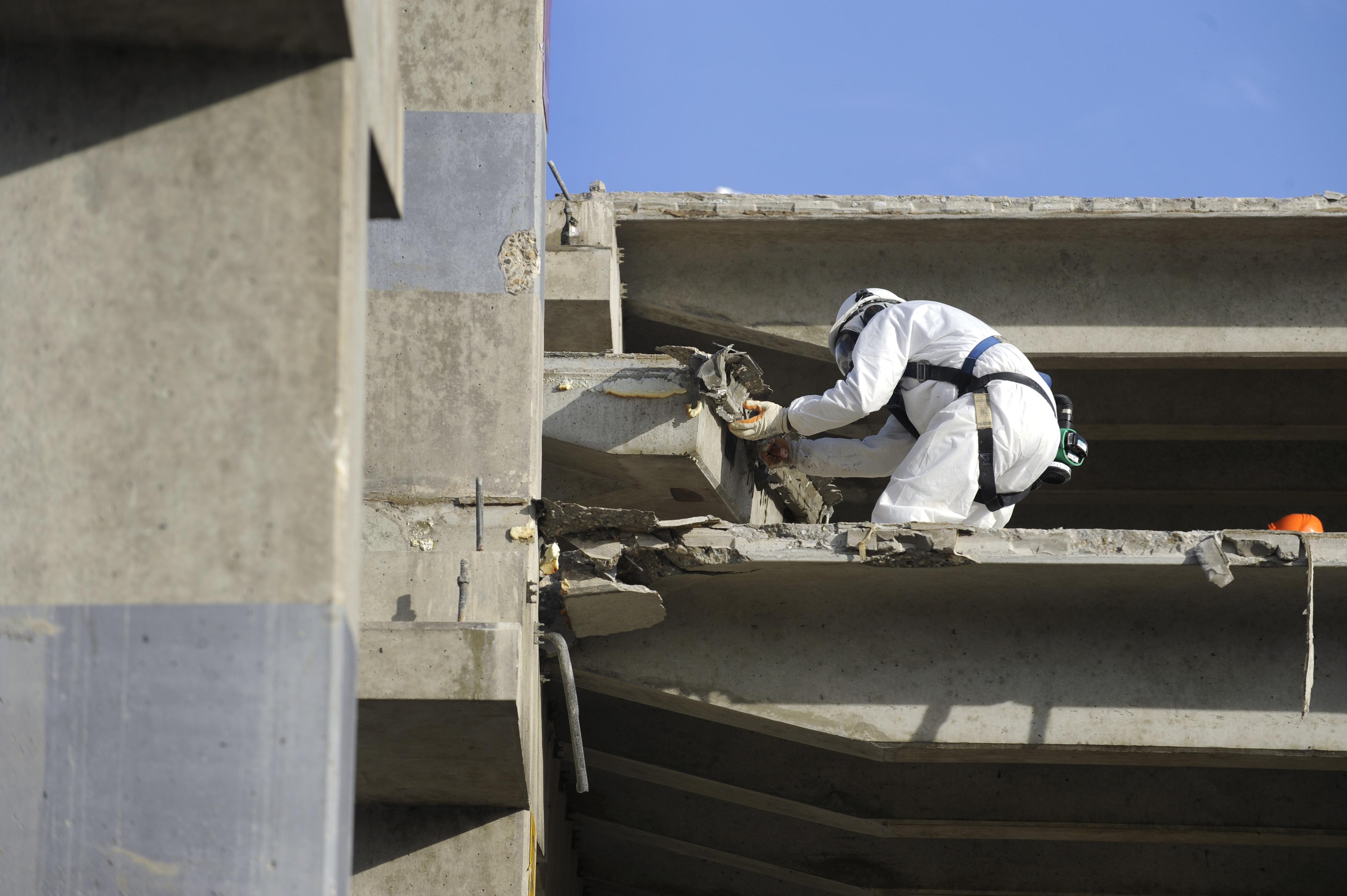 <p>Een asbestsaneerder verwijdert zorgvuldig de asbesthoudende stelplaten die gebruikt zijn bij de uitbreiding van de parkeergarage in 1982.</p>