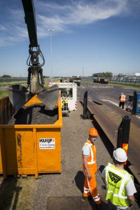 Direct naast de weegbrug staat een container met gefreesd asfalt en een overslagkraan. De kraan haalt materiaal uit de vrachtwagen of laadt bij. Aan de voorzijde van de weegbrug staat een kleine container met daarin de computer.