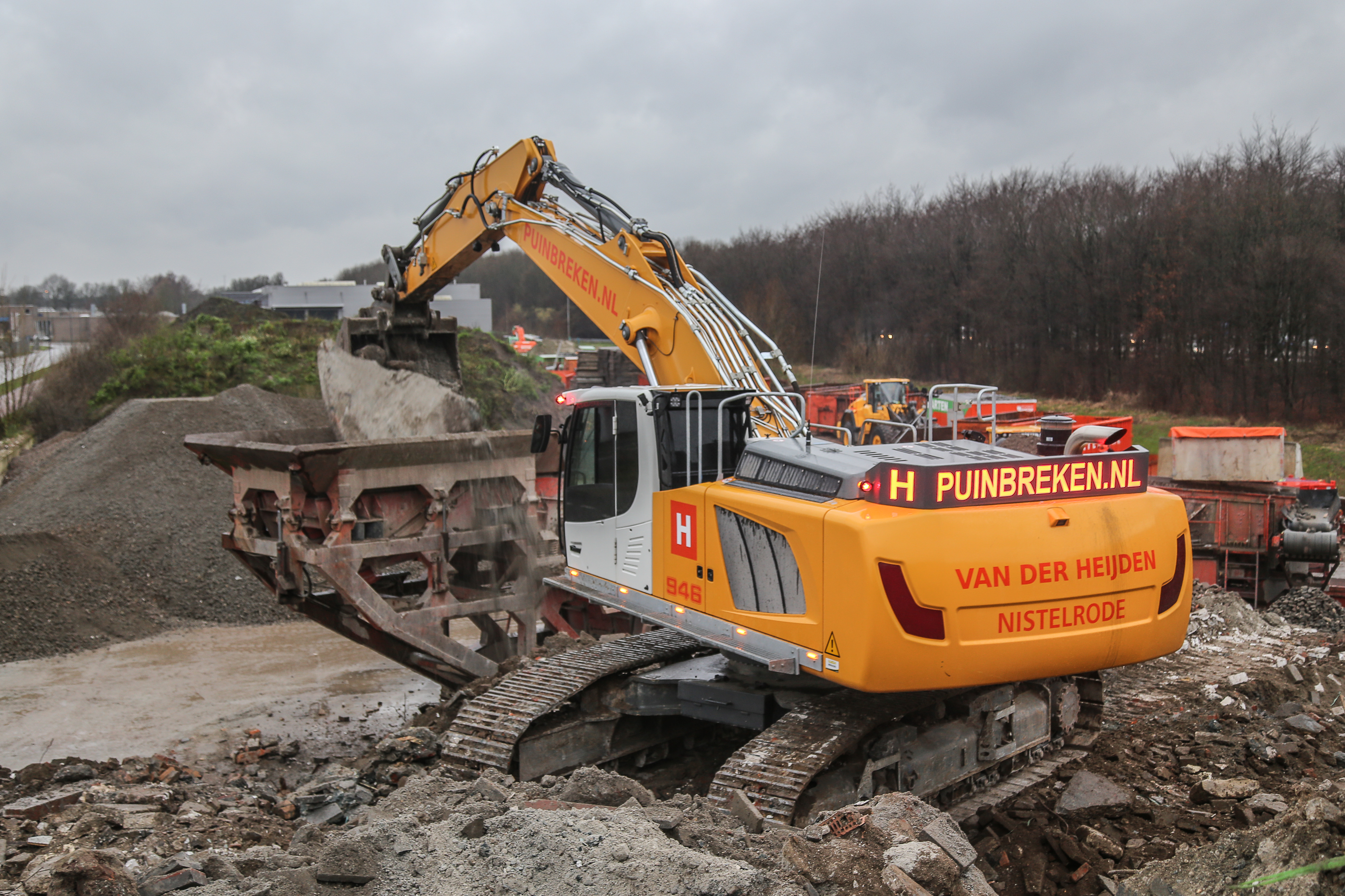 <p>Grote schollen beton verdwijnen in de breker. Die Van der Heijden zelf bouwde.</p>