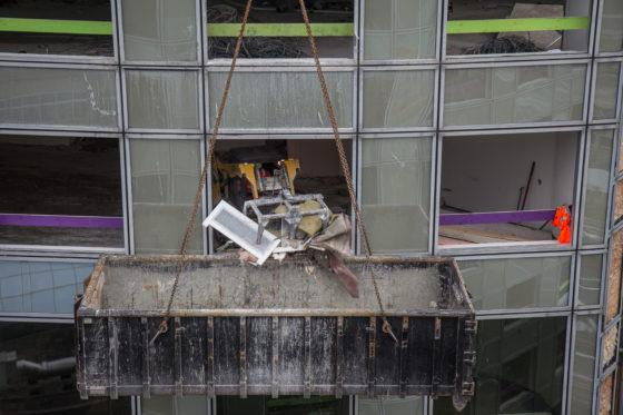 Een schranklader stript alle gebouwen. Daarna worden de nodige constructieve aanpassingen gedaan, later kan de aannemer aan de slag.