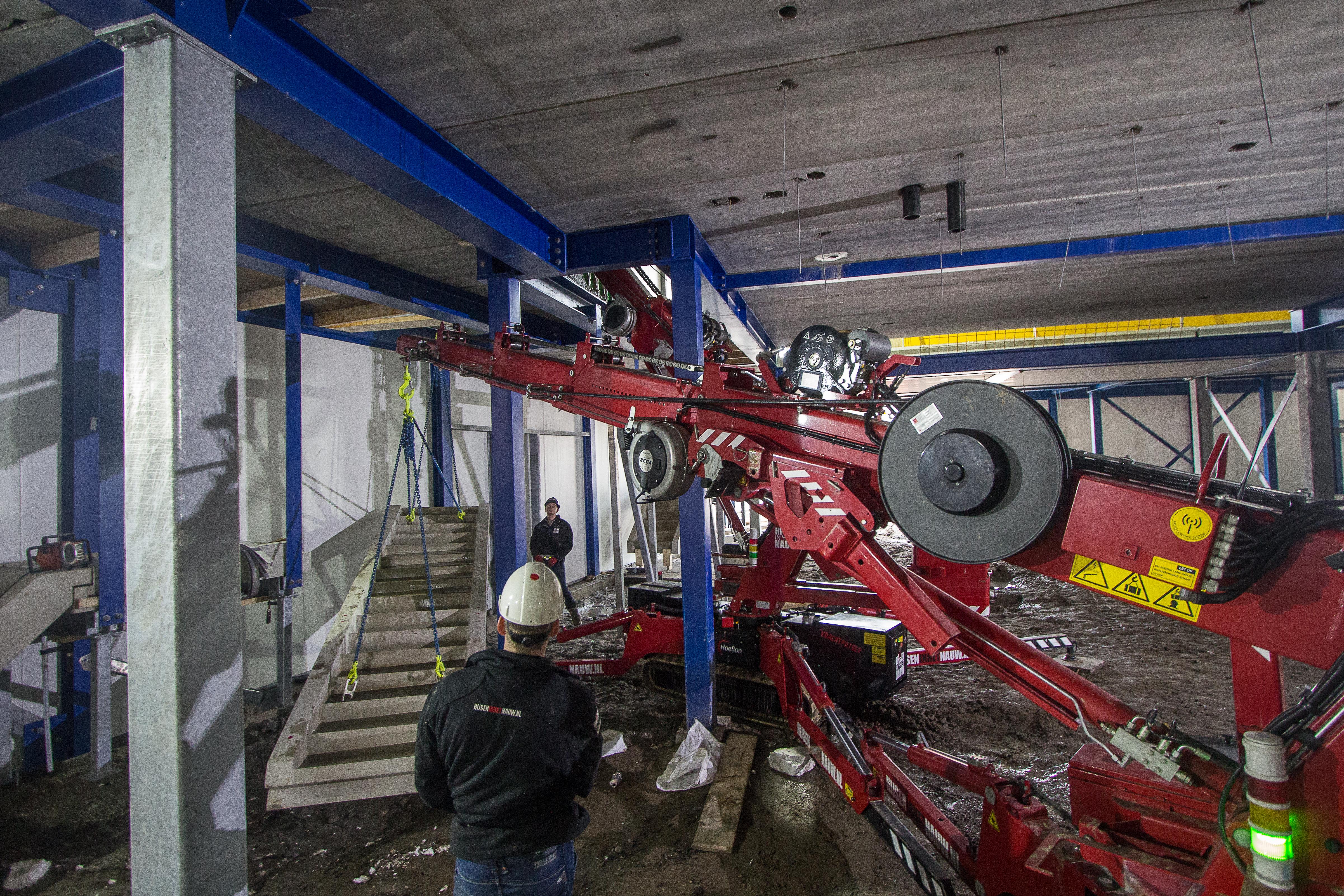 <p>De tandemhijs is teamwerk. Tussen de staanders door wordt het betonnen trapelement op z'n plek gelegd. Ook op vlucht staan de kleine kranen hun mannetje.</p>