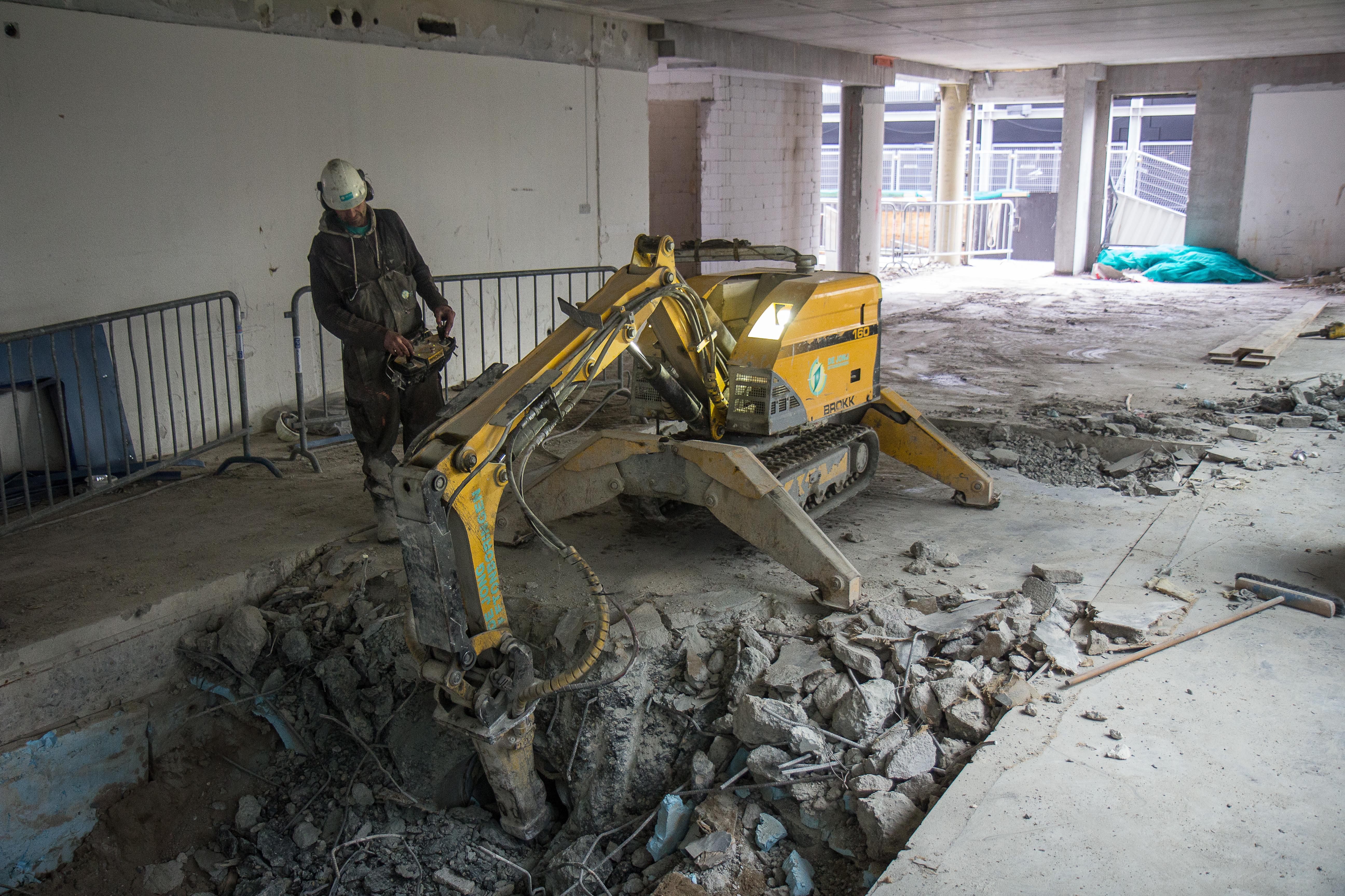 <p>De Jong hakt de 40 centimeter dikke vloer, met onderliggend luchtkanaal, vrij. Zo kan de fundering van het gebouw verzwaard worden.</p>