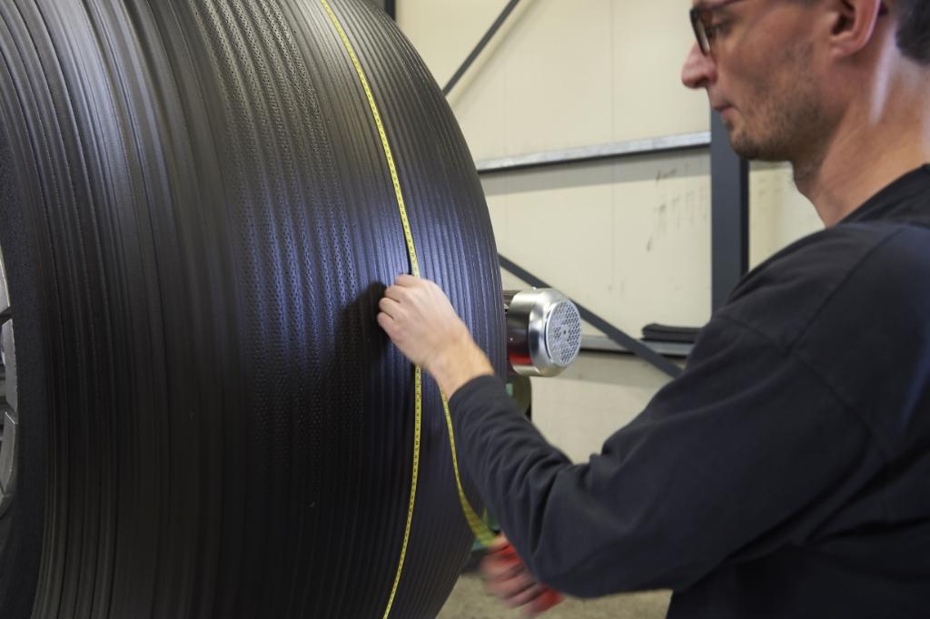 <p>Met een meetlint wordt gecontroleerd of er genoeg rubber voor het loopvlak is aangebracht. Als er te weinig rubber wordt gebruikt, wordt de mal straks niet volledig gevuld. Te veel rubber is een verspilling van materiaal en arbeid. </p>