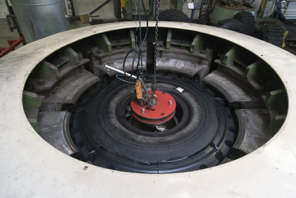 <p>Het vulkaniseren duurt &#8211; afhankelijk van de gebruikte hoeveelheid rubber en de bandenmaat – twee tot soms wel vier uur. Wanneer het proces gereed is, wordt de deksel van de pers gehaald en wordt de nieuwbakken band eruit getakeld. </p>