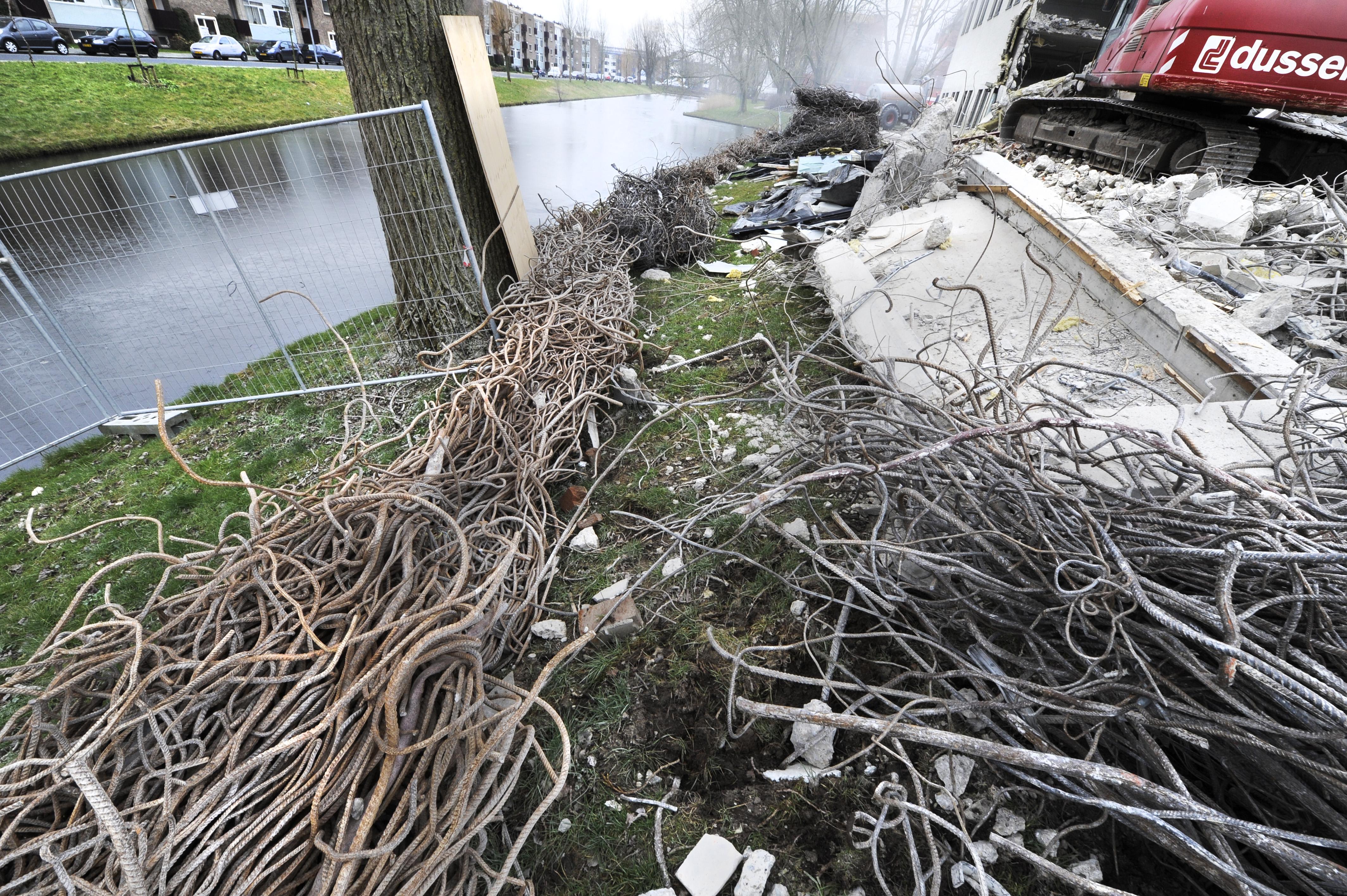<p>Om te voorkomen dat puin in de aangrenzende vijver beland zijn dikke bossen ijzer, afkomstig uit het kantoorcomplex, als een barrière langs de rand van het water gelegd.</p>
