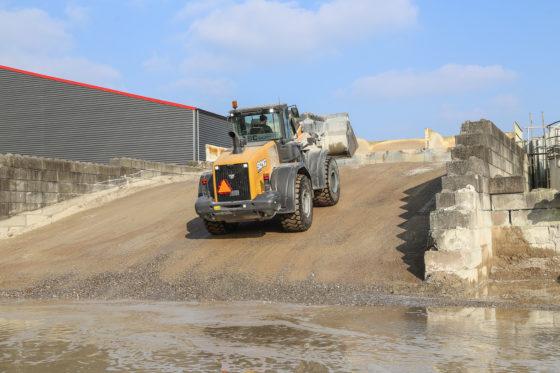 De bunkers zijn te bereiken via het steile talud. Hoewel de wiellader praktisch alleen overslagwerk doet, is toch gekozen voor een snelwissel. Zo kan de veegmachine er snel aan om het terrein schoon te houden.