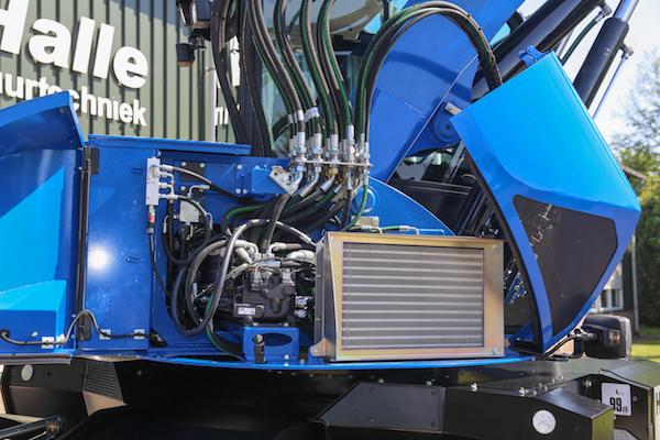 <p>De hydrauliek, aansturing en bediening is eigen Hobelman-ontwerp. De koeler die je ziet is de condensator van de airco. Motor, hydrauliek en bijgehorende koeling is in de onderwagen gebouwd.</p>