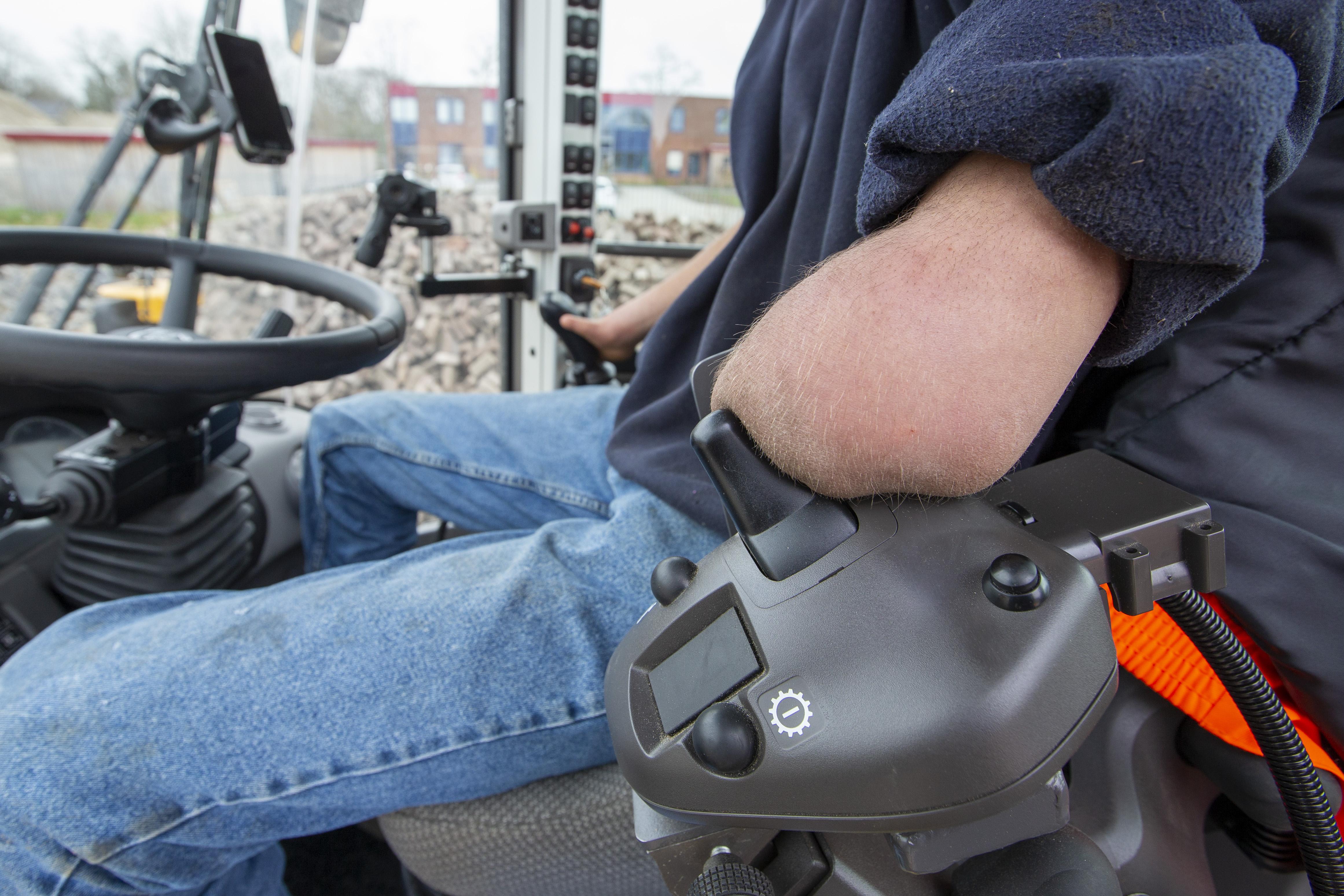 <p>Op de linkerarmconsole is een knop gemaakt, waarmee Jens voor- of achteruitrijden kan inschakelen. </p>