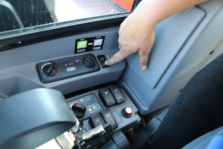 Via het bovenste bedieningspaneel kan onder meer de airconditioning worden bediend. Het onderste paneel herbergt de knop voor de (traploze) bediening van de rijsnelheid en bedieningsknoppen voor onder meer de ecostand, zwaailamp en de werkverlichting.