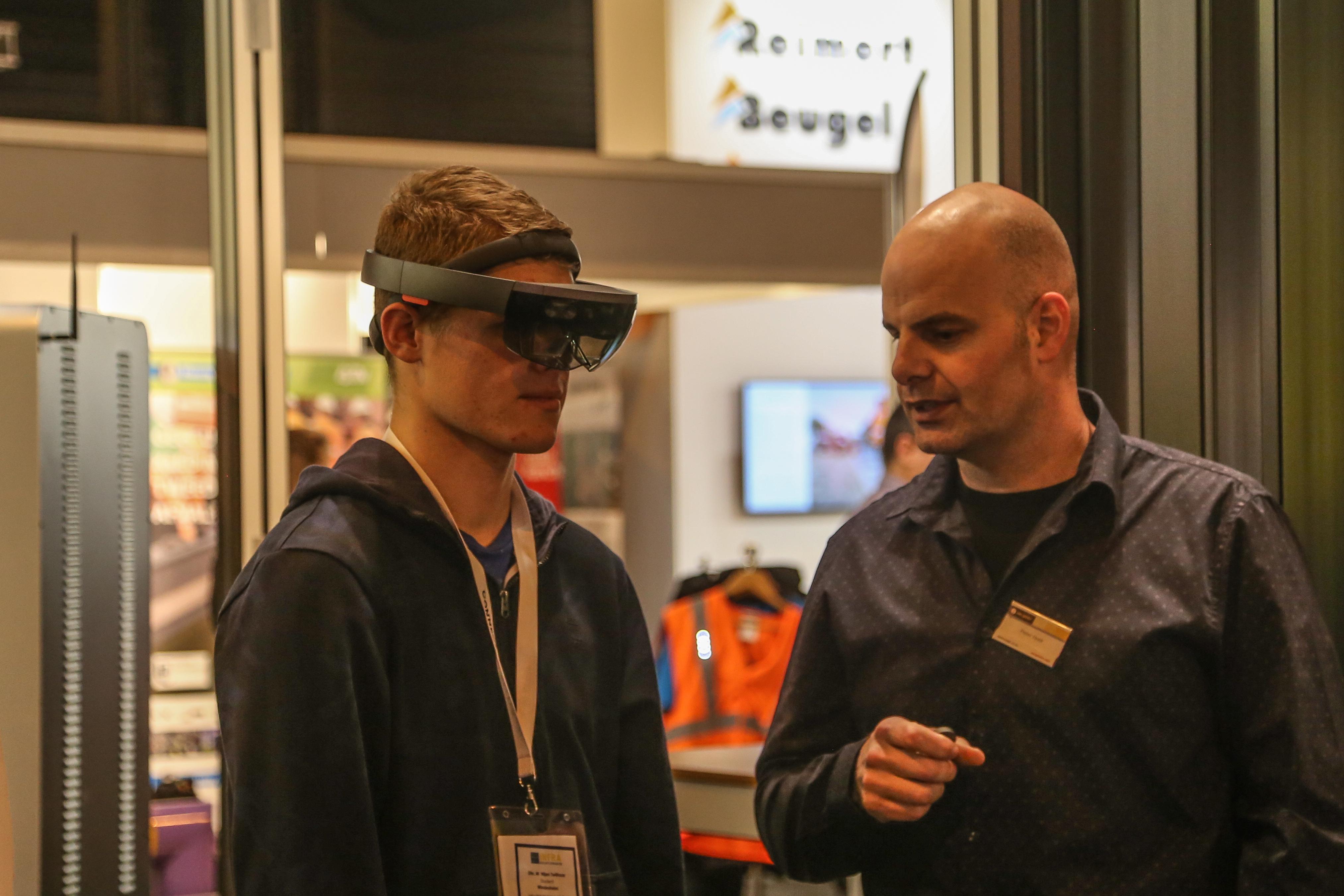 <p>Pieter Hoek van infrabedrijf Van Gelder laat een student zien hoe deze augmented reality-bril werkt. Ook is er een interactieve quiz op de stand. Met Gelderpoort heeft het bedrijf al jaren een eigen opleidingsinstituut. Grote wens is dat mbo'ers hier direct na hun studie zouden kunnen starten, nu mag dat pas vanaf hun 18e jaar.</p>